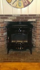 Wood stove installed in a stone fireplace